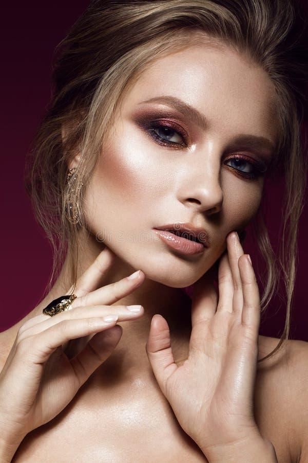 Härlig flicka med perfekt hud, färgrikt smink, aftonfrisyr Härlig le flicka fotografering för bildbyråer