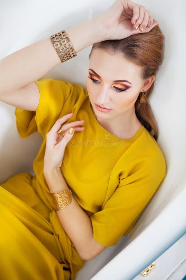 Härlig flicka med sminket som bär den långa gula klänningen fotografering för bildbyråer