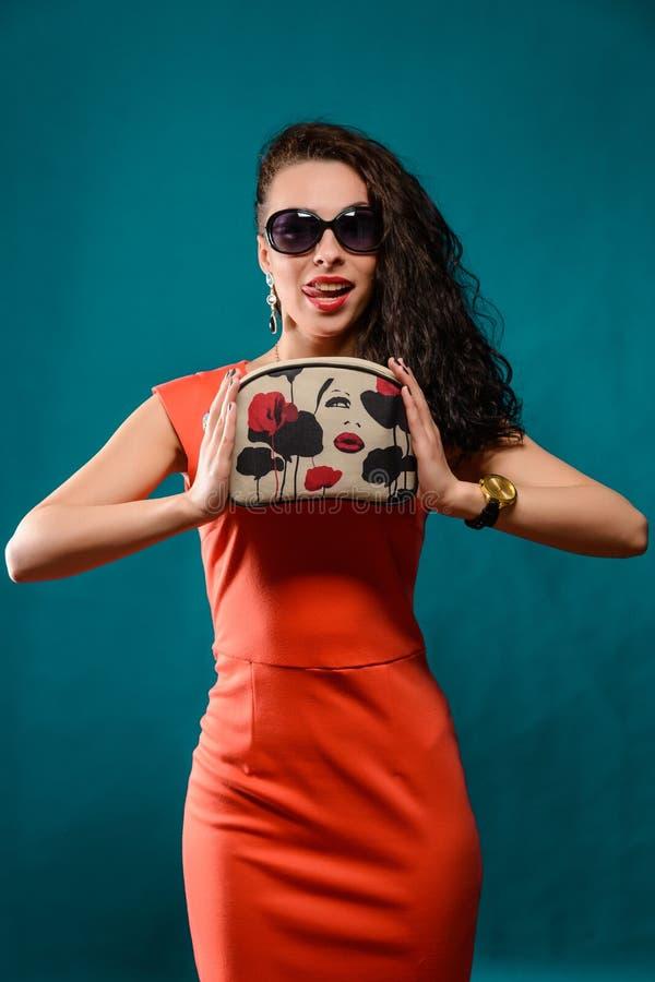 Härlig flicka med solglasögon och kopplingpåse royaltyfria bilder