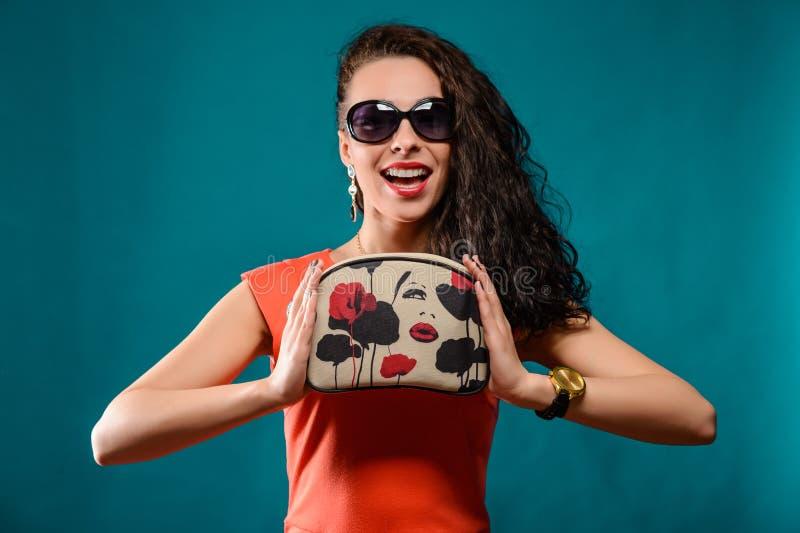 Härlig flicka med solglasögon och kopplingpåse fotografering för bildbyråer