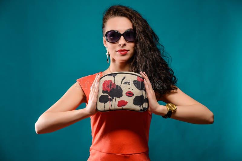 Härlig flicka med solglasögon och kopplingpåse royaltyfri bild
