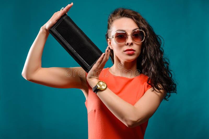 Härlig flicka med solglasögon och kopplingpåse arkivbild