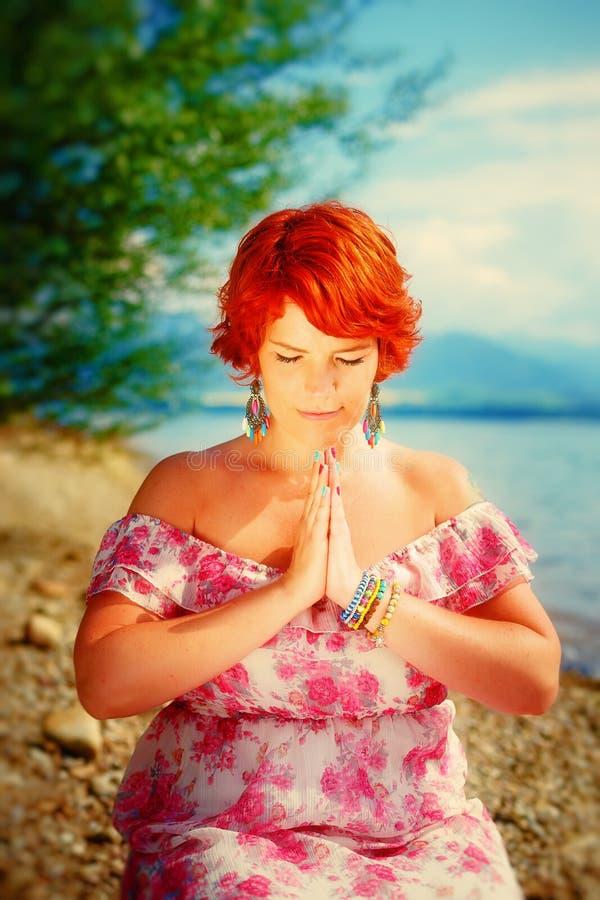 Härlig flicka med strålningsrött hår i sommerklänning i en meditativ andlig gest av bönen royaltyfri bild