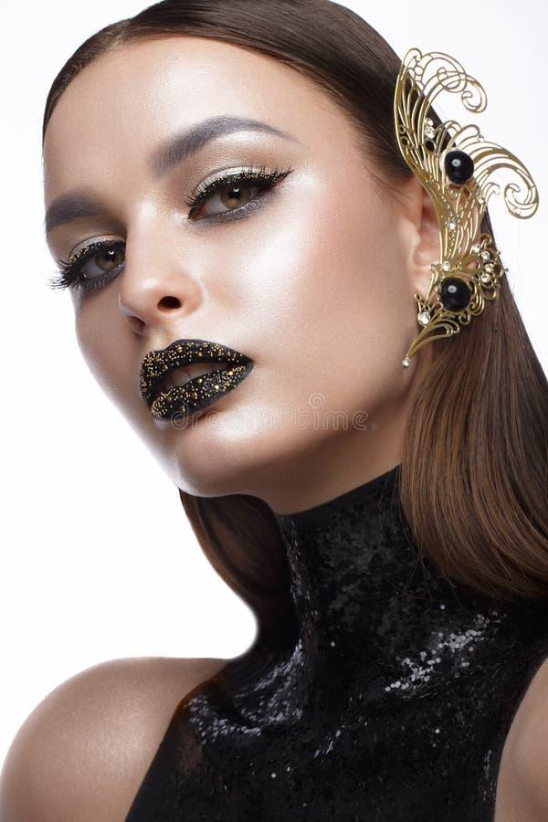 Härlig flicka med svart idérikt konstsmink och guldtillbehör Härlig le flicka royaltyfria bilder