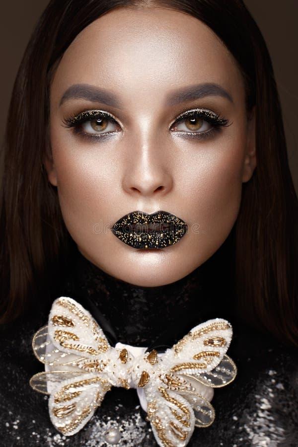 Härlig flicka med svart idérikt konstsmink och guldtillbehör Härlig le flicka royaltyfri fotografi