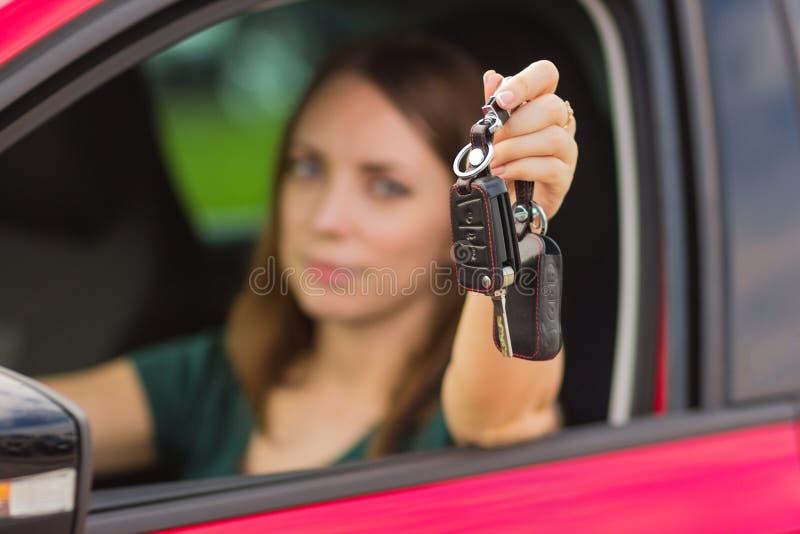 Härlig flicka med tangenter från bilen i handen, begrepp av att köpa en ny bil, känslor av glädje från shopping royaltyfri foto