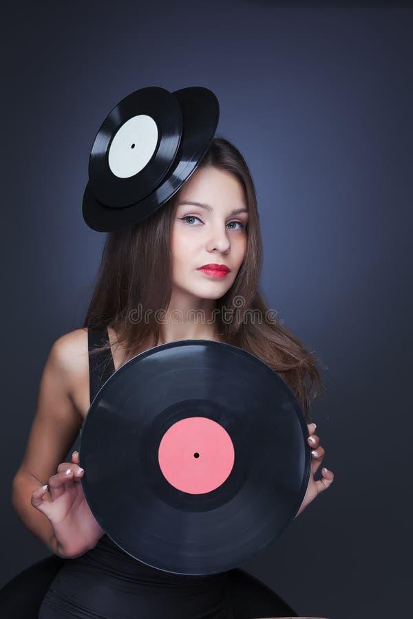 Härlig flicka med vinildisketten på svart bakgrund royaltyfri foto