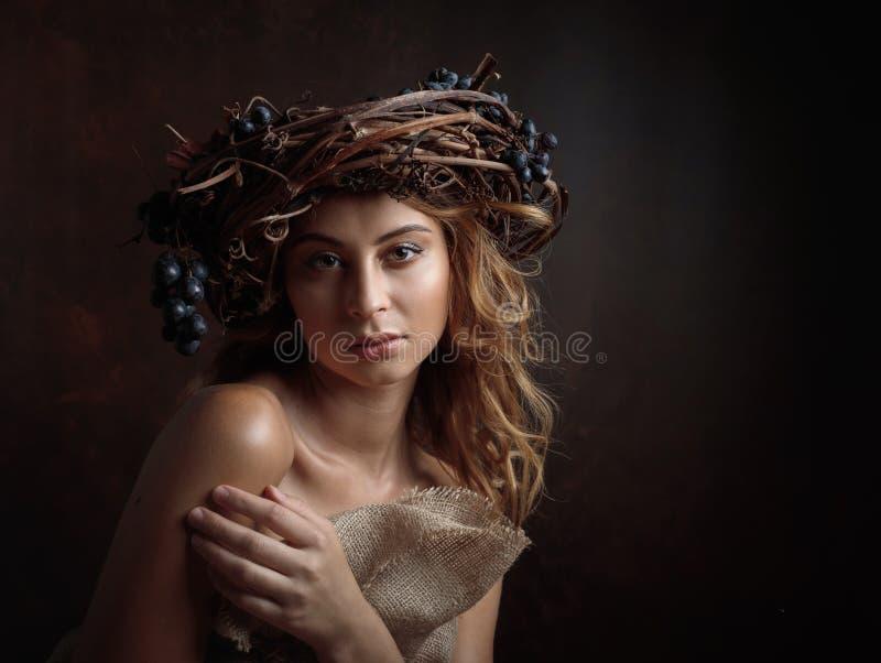 Härlig flicka med vinrankakrans- och blåttdruvor royaltyfri bild