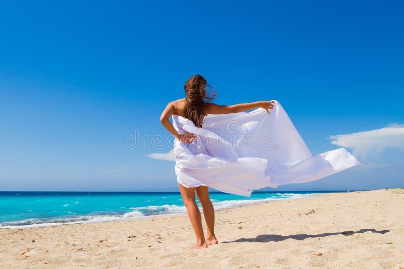 Härlig flicka med vitt tyg på stranden. royaltyfri bild