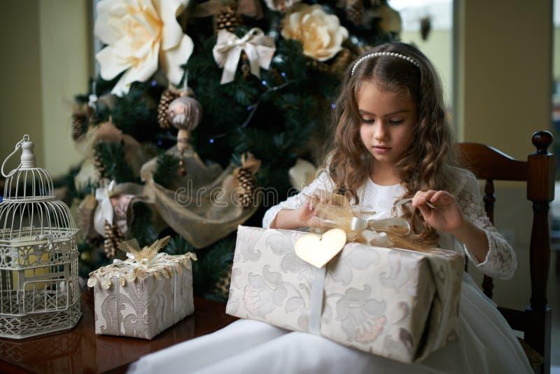 Härlig flicka nära julgranen som packar upp gåvor royaltyfri fotografi
