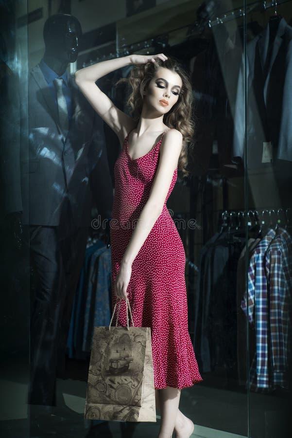 Härlig flicka nära shoppingfönster royaltyfria bilder