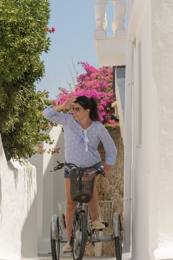 Härlig flicka och cykel mot en färgrik bakgrund på den Andros ön i Grekland royaltyfri fotografi