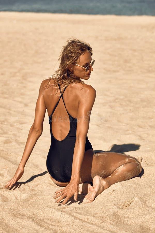 Härlig flicka på den sandiga stranden, i baddräkt och att solbada royaltyfri bild