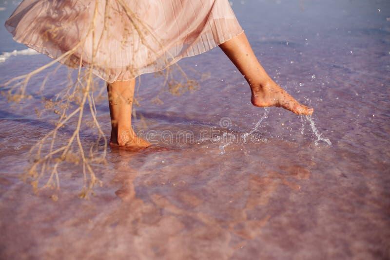 Härlig flicka på en rosa sjö arkivbild