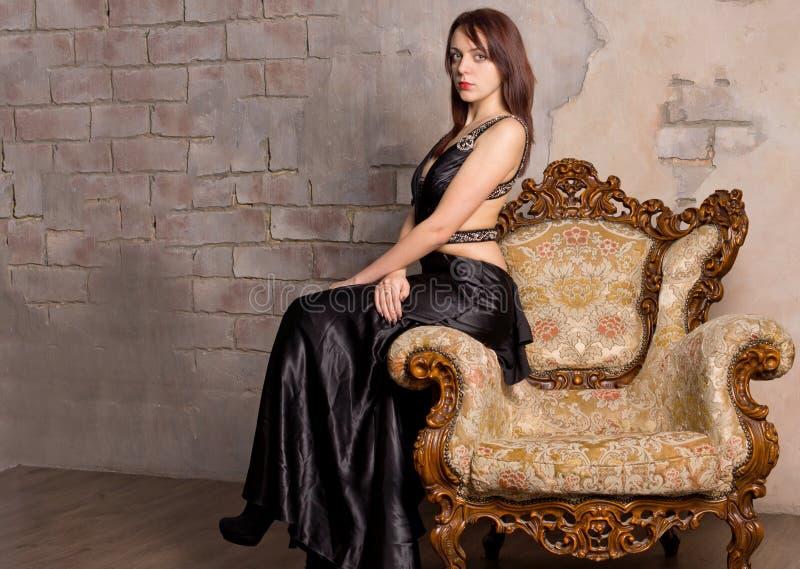 Härlig flicka på en tappningfåtölj royaltyfria foton