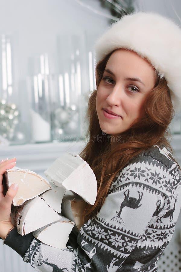 Härlig flicka på en vinterdag med högen av vedträt på händer royaltyfri bild