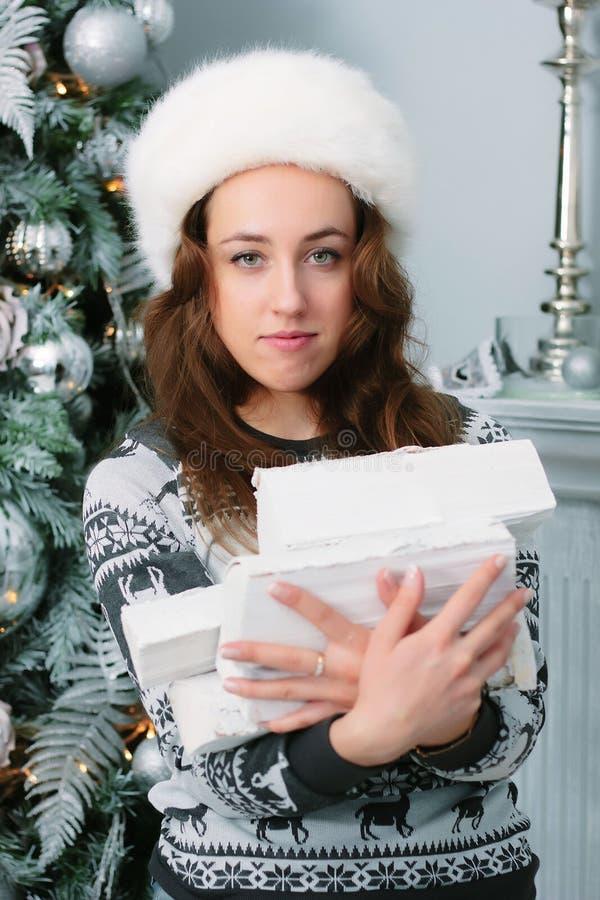 Härlig flicka på en vinterdag med högen av vedträt på händer arkivfoton