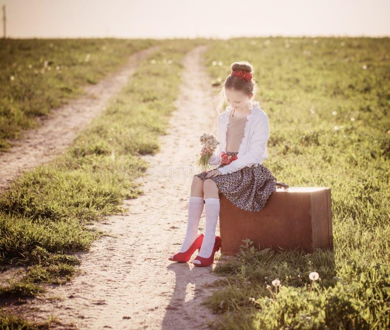 Härlig flicka på resväskan med blommor royaltyfria bilder