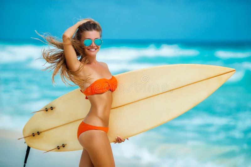 Härlig flicka på stranden med surfingbrädan arkivfoton