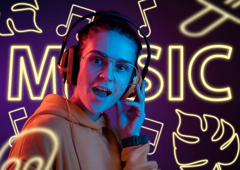 Härlig flicka på studiobakgrund i neonljus arkivfoto