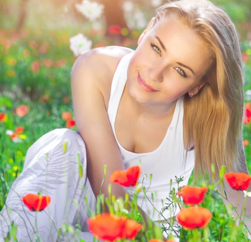Härlig flicka på vallmoblommafält arkivfoto