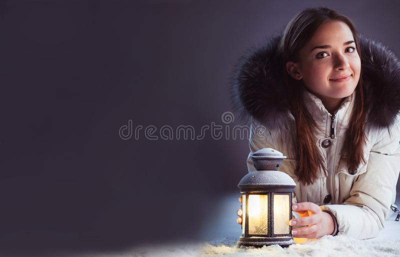 Härlig flicka på vintersnö med jullyktan royaltyfri fotografi