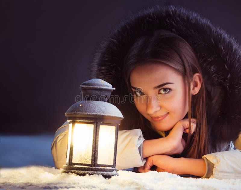 Härlig flicka på vintersnö med lyktan arkivbilder