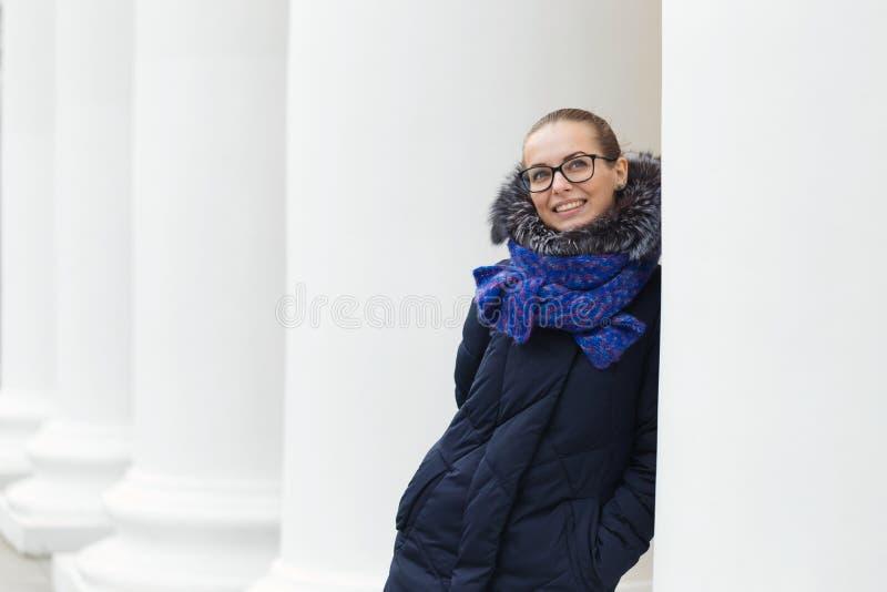 Härlig flicka som är gladlynt med vita kolonner utomhus arkivbilder
