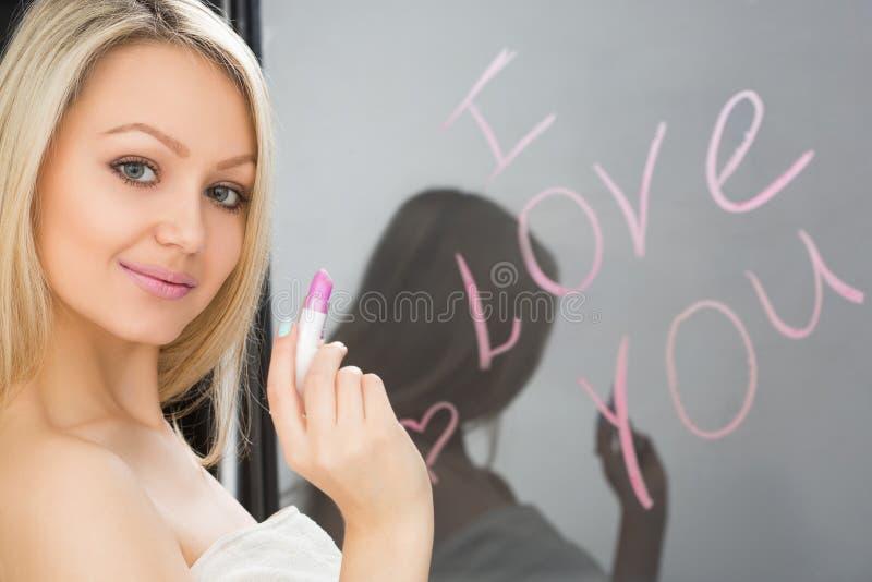 Härlig flicka som är skriftlig på en spegel i läppstift, I fotografering för bildbyråer