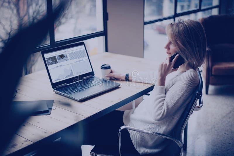 Härlig flicka som använder bärbara datorn och smartphonen på trätabellen i coworking studio Begrepp av ungdomarsom arbetar med royaltyfria bilder