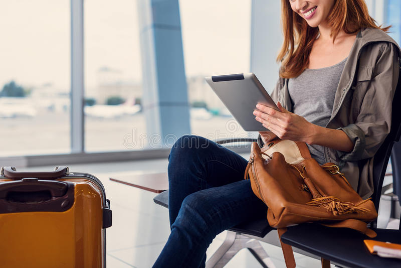 Härlig flicka som använder minnestavlan i flygplats arkivbild