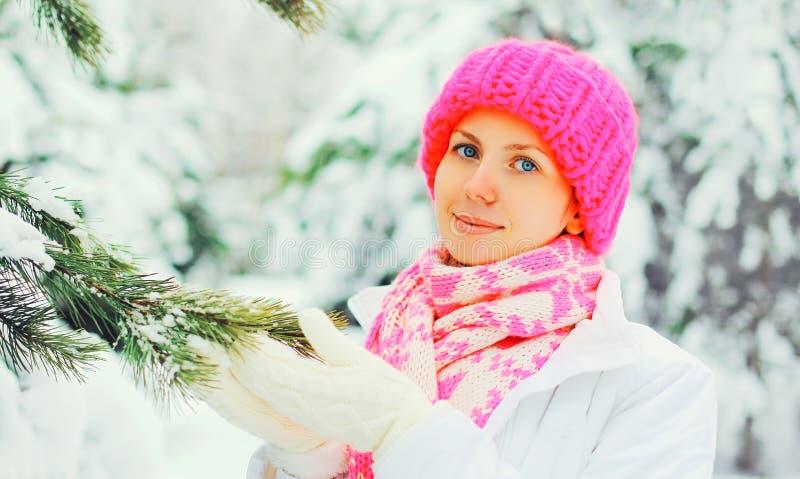 Härlig flicka som bär den färgrika stack hatthalsduken nära julträd royaltyfria bilder