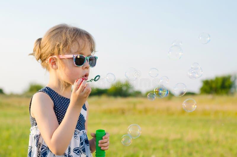Härlig flicka som blåser bubblor i naturen, fritt utrymme royaltyfri foto