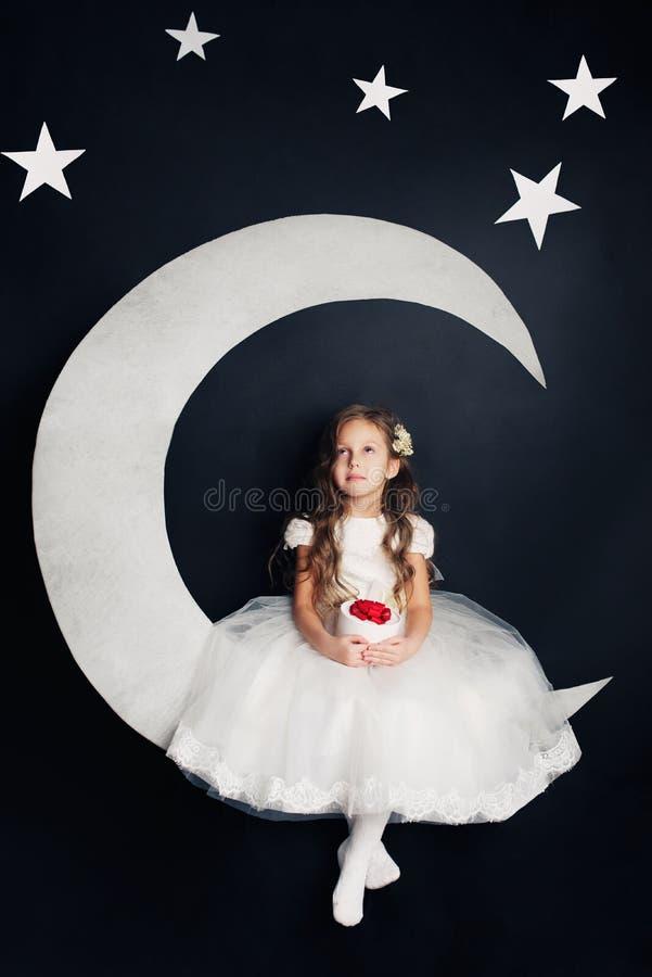 Härlig flicka som drömmer på månen royaltyfria bilder