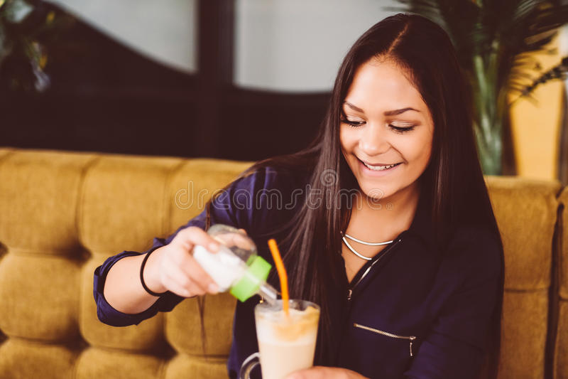 Härlig flicka som dricker ismockaskakan i ett kafé royaltyfri bild