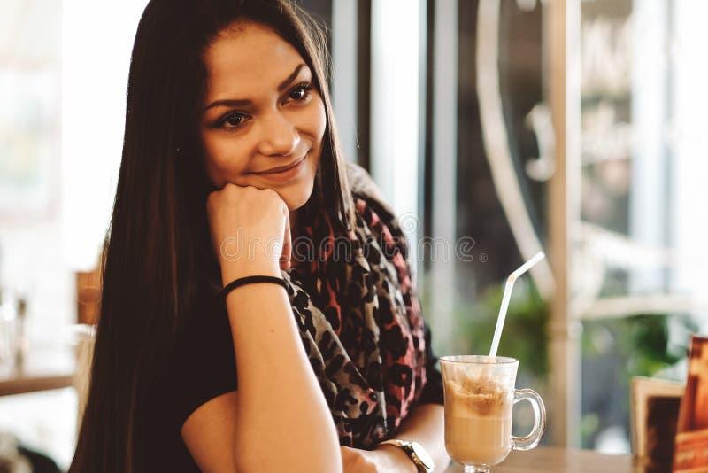 Härlig flicka som dricker ismockaskakan i ett kafé royaltyfri foto