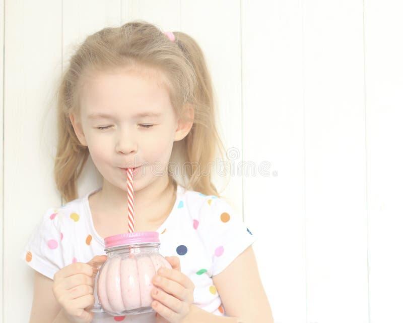 Härlig flicka som dricker smoothieskakan arkivbilder