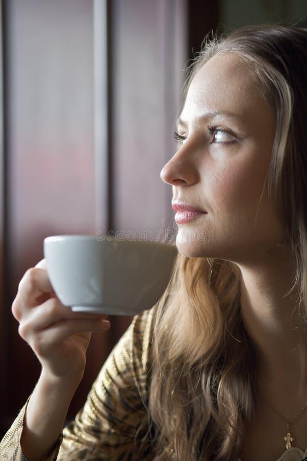 Härlig flicka som dricker te eller kaffe i kafé arkivfoto