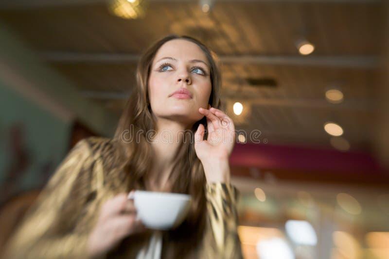 Härlig flicka som dricker te eller kaffe i kafé royaltyfri fotografi