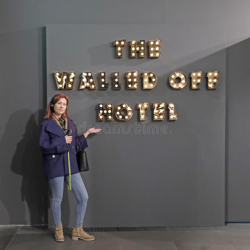 Härlig flicka som framlägger 'det walled av hotellet 'i Banksy en obehörig utställning royaltyfria bilder