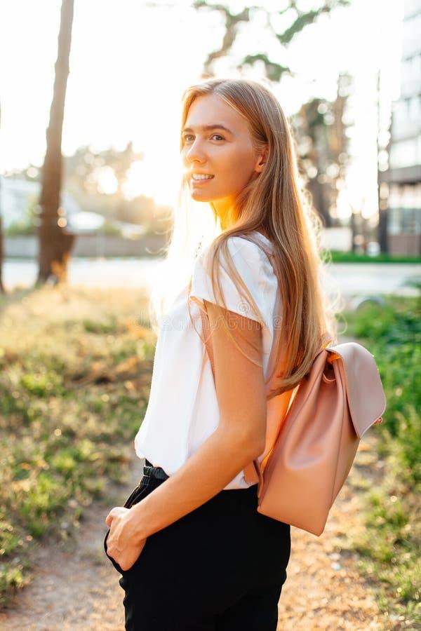Härlig flicka som går runt om stad i den vita t-skjortan, stadsbackpa royaltyfri bild