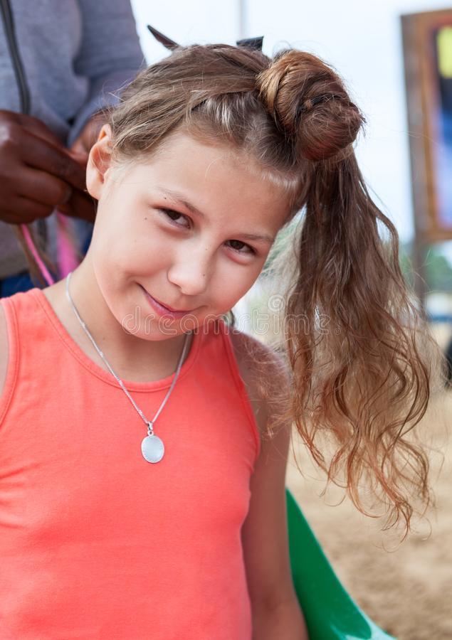 Härlig flicka som gör frisyren Frisör som startar att göra den afroed frisyren fotografering för bildbyråer