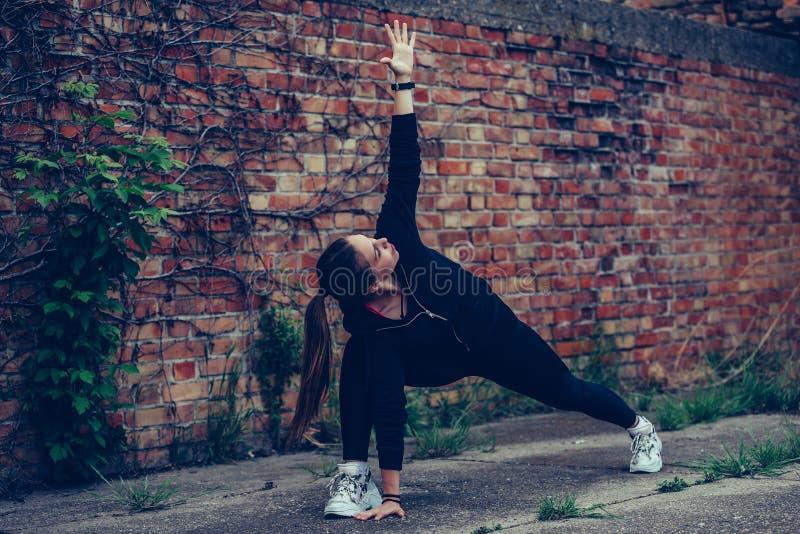 Härlig flicka som gör sträcka övningar, tegelstenvägg i bakgrunden royaltyfri bild