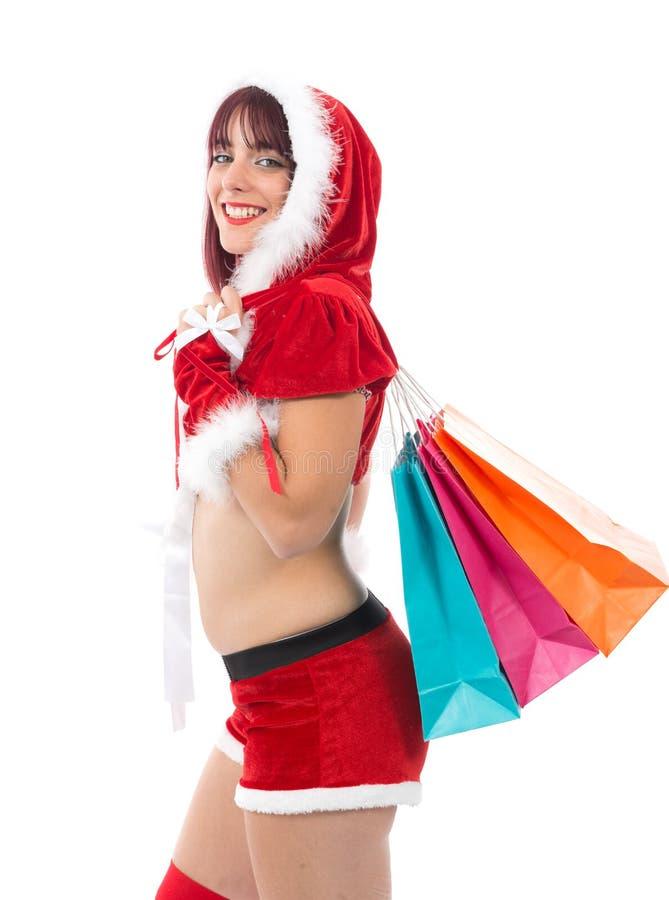 Härlig flicka som kläs som jultomten med julklappar royaltyfri bild
