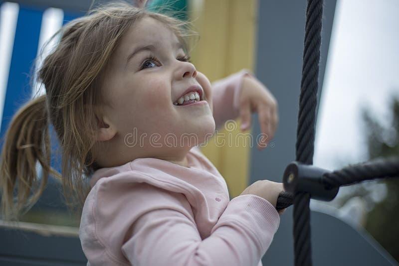 Härlig flicka som klättrar repet i lekplatsen royaltyfri bild
