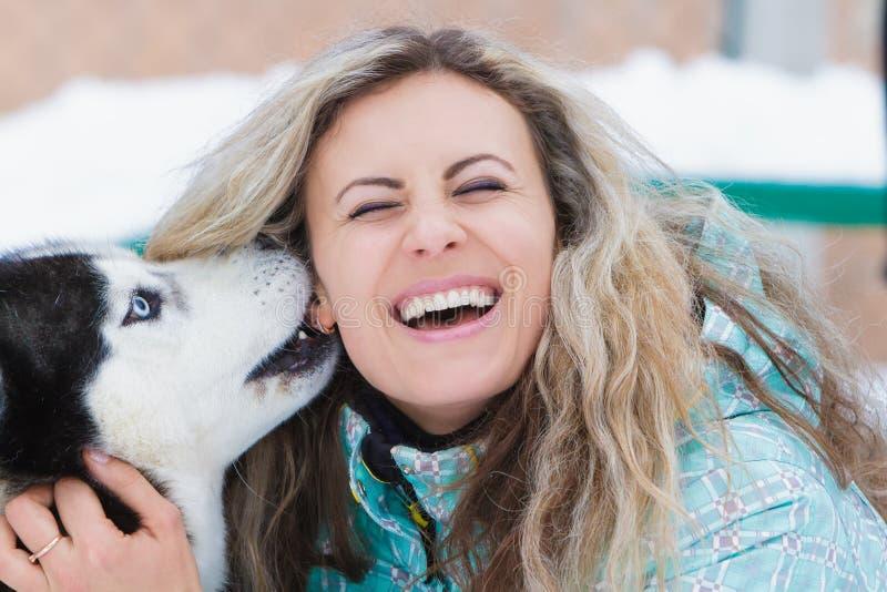 Härlig flicka som kramar hunden i vinter royaltyfri bild