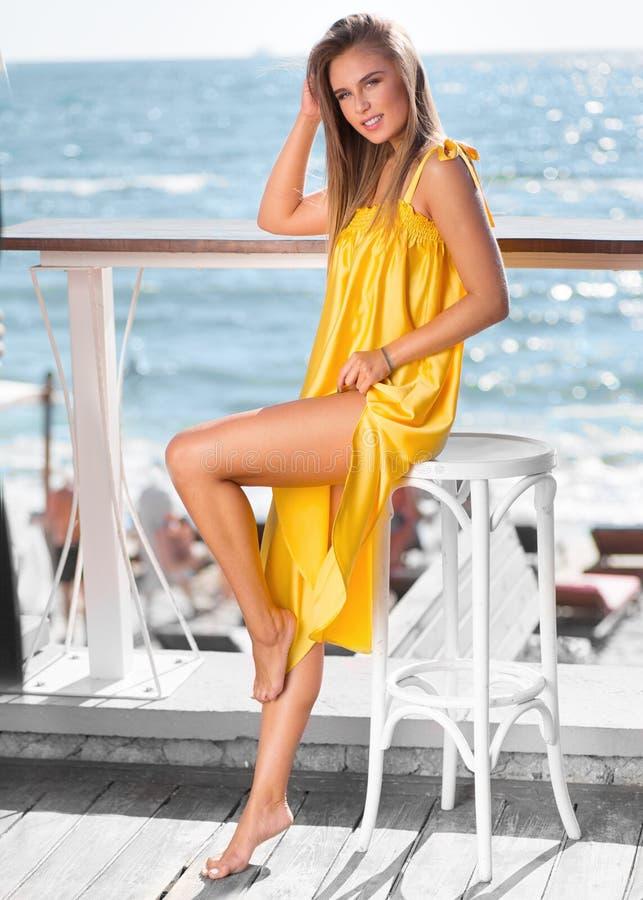 Härlig flicka som ler i en gul klänning arkivbilder