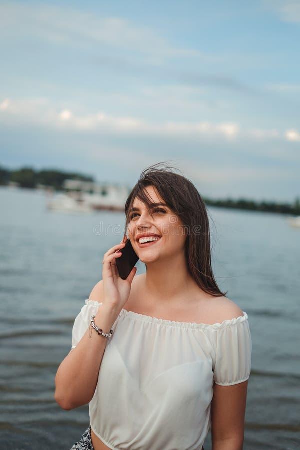 Härlig flicka som ler, medan tala på telefonen vid floden arkivfoton