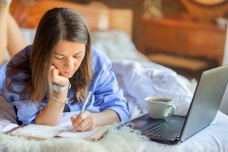 Härlig flicka som ligger i säng bredvid en bärbar dator arkivbild
