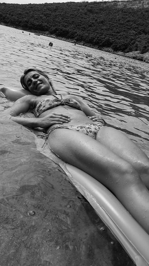 Härlig flicka som ligger på en madrass i vatten royaltyfri fotografi